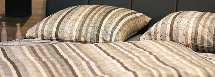 Een bed waarop twee kussens liggen
