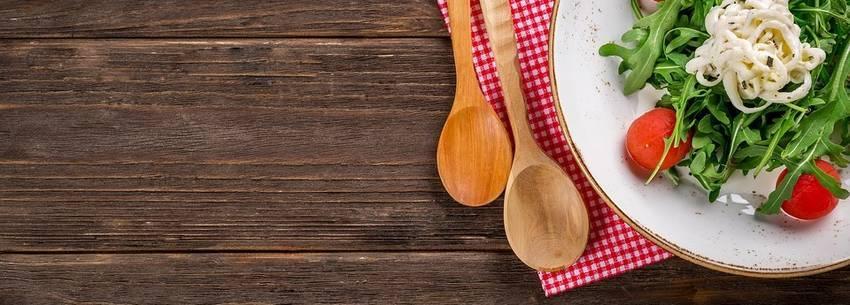 Een eettafel van hout met eten er op