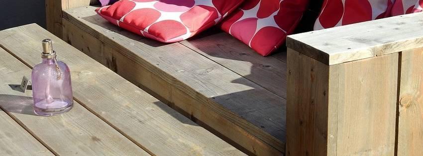 Een hoekbank van steigerhout waarop kussens liggen