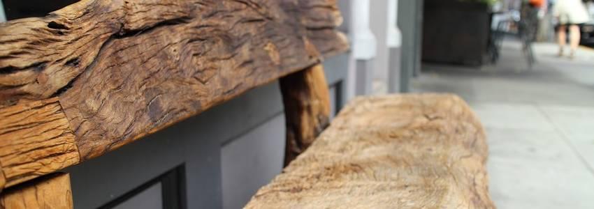 Een verweerde houten bank die op straat staat