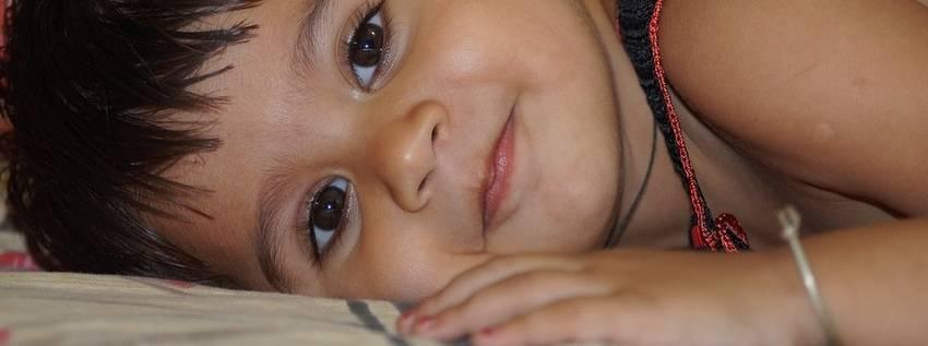 Een kind dat in z'n bedje ligt te lachen